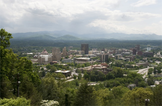 Photo of Asheville, North Carolina showing its buildings, city and currounding forests and hills, and  mountains